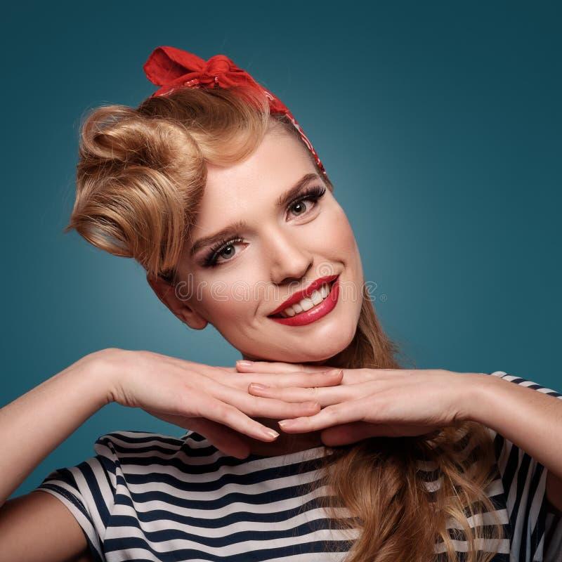 Χαμογελώντας pinup κορίτσι ομορφιάς στο μπλε υπόβαθρο στοκ φωτογραφία