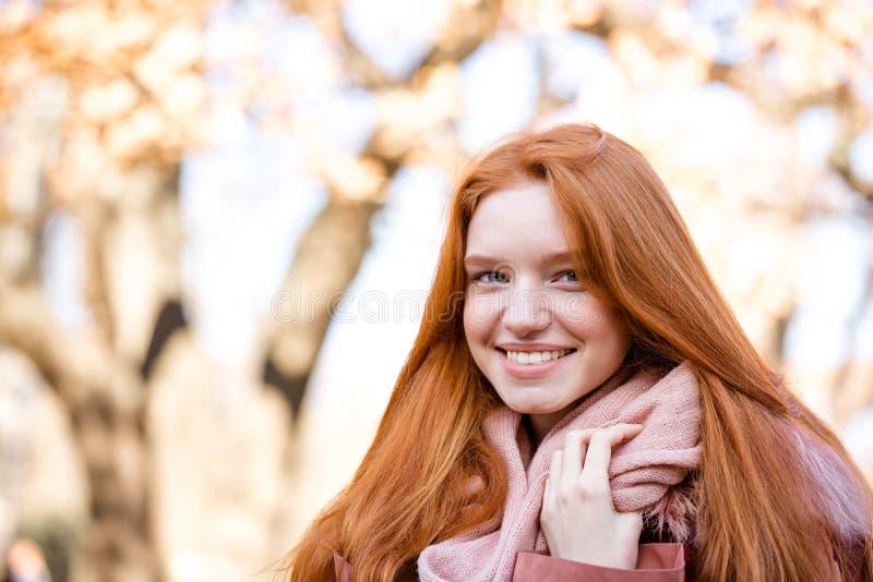 Χαμογελώντας redhead γυναίκα που εξετάζει τη κάμερα υπαίθρια στοκ φωτογραφία με δικαίωμα ελεύθερης χρήσης