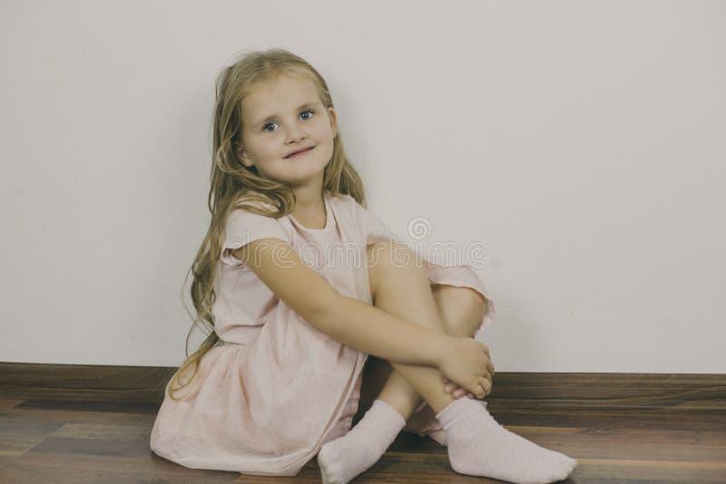 Χαμόγελα κοριτσιών μελαγχολικά, που κάθονται στο πάτωμα στοκ φωτογραφίες