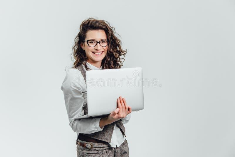 Χαμόγελα νέων κοριτσιών BBeautiful Εργασίες για ένα lap-top στα γυαλιά και ένα άσπρο πουκάμισο στοκ φωτογραφία