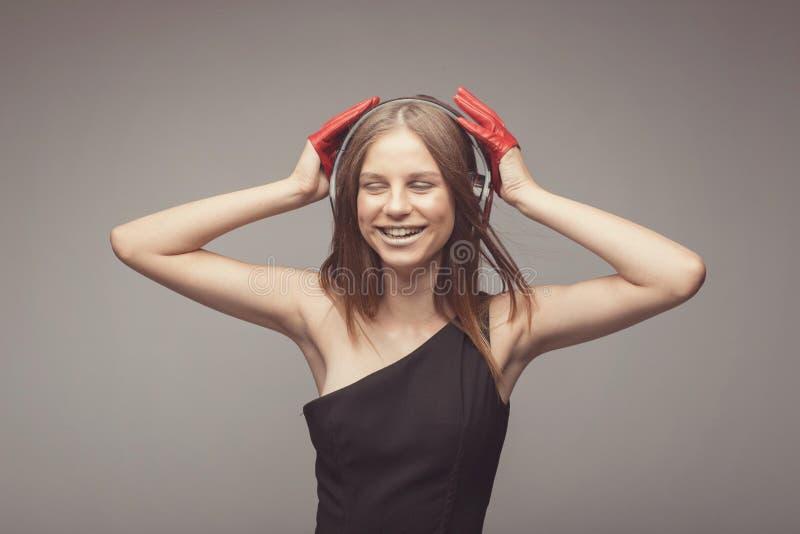 Χαμόγελου η ελκυστική μουσική ακούσματος κοριτσιών μόδας όμορφη με τα ακουστικά, που φορούν τα κόκκινα γάντια, παίρνει την ευχαρί στοκ εικόνες