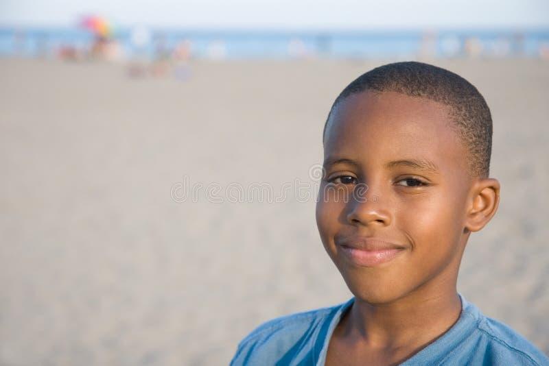 χαμόγελο αγοριών s παραλι στοκ φωτογραφία