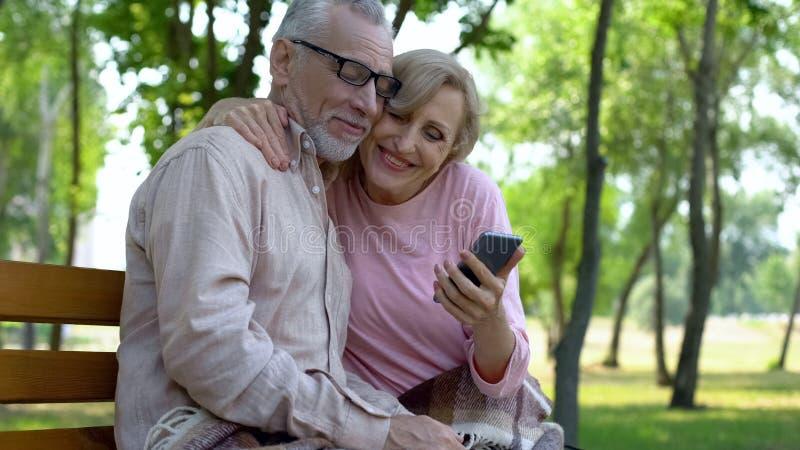 Χαμόγελο αποσυρμένο smartphone εκμετάλλευσης γυναικών και αγκάλιασμα του όμορφου συζύγου, app στοκ φωτογραφία