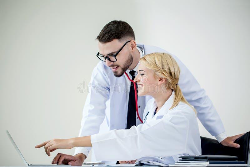 χαμόγελο γιατρών ανδρών και γιατρών γυναικών που λειτουργεί μαζί στο lap-top ι στοκ φωτογραφία