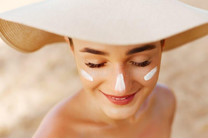 Χαμόγελο γυναικών ομορφιάς που εφαρμόζει την κρέμα ήλιων στο πρόσωπο r Προστασία ήλιων σώματος sunscreen στοκ φωτογραφία με δικαίωμα ελεύθερης χρήσης