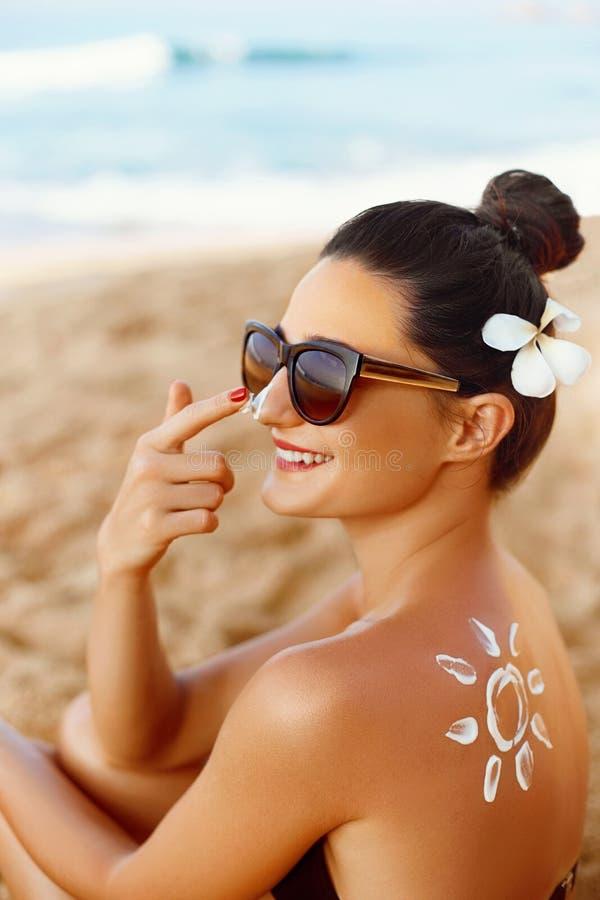 Χαμόγελο γυναικών που εφαρμόζει την κρέμα ήλιων στο πρόσωπο Skincare Προστασία ήλιων σώματος sunscreen Θηλυκό ενυδατικό λοσιόν κη στοκ εικόνες