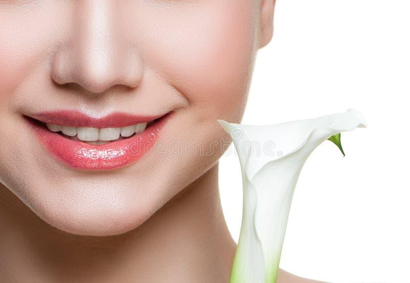 Χαμόγελο γυναικών τα άσπρα δόντια και τα λουλούδια που απομονώνονται με στοκ φωτογραφία
