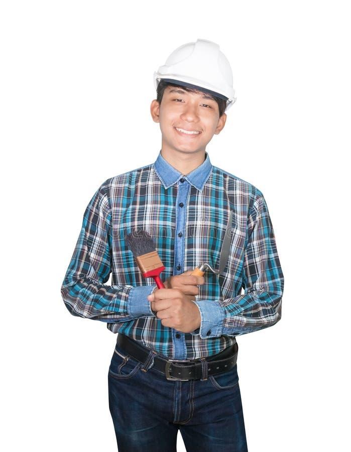 Χαμόγελο μηχανικών με το τρίγωνο εκμετάλλευσης χεριών trowel και το άσπρο πλαστικό κρανών ασφάλειας ένδυσης βουρτσών χρωμάτων στο στοκ εικόνες με δικαίωμα ελεύθερης χρήσης