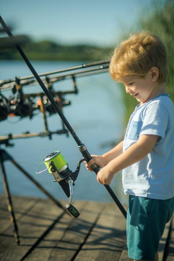 Χαμόγελο παιδιών με την αλιεία της ράβδου στην ξύλινη αποβάθρα στοκ εικόνες