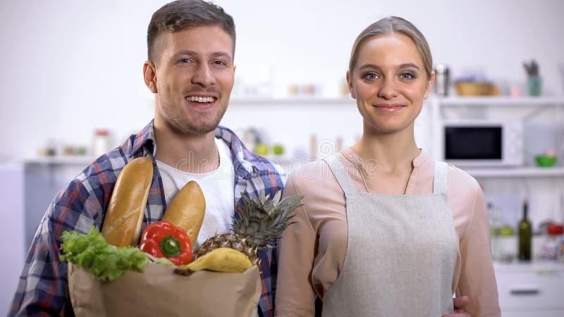 Χαμόγελο της τσάντας εγγράφου εκμετάλλευσης ζευγών των παντοπωλείων, υγιής τρόπος ζωής, μαγείρεμα στοκ φωτογραφία με δικαίωμα ελεύθερης χρήσης