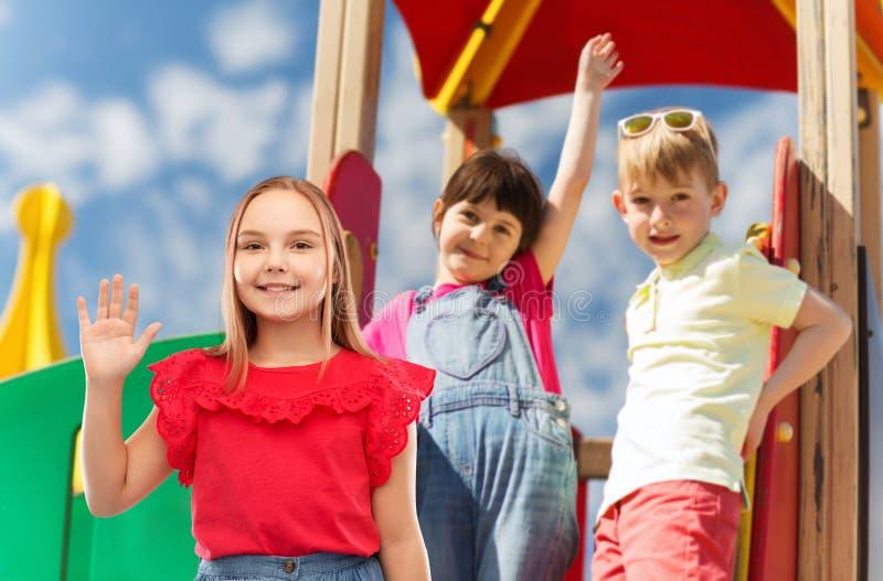 Χαμόγελο του κυματίζοντας χεριού κοριτσιών στην παιδική χαρά παιδιών στοκ εικόνες