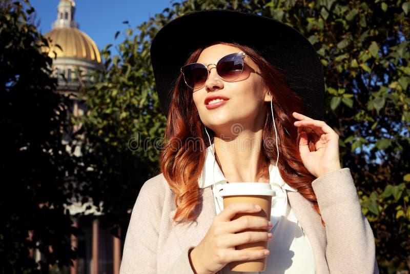 Χαμόγελο του μοντέρνου νέου καφέ κατανάλωσης γυναικών περπατώντας σε μια οδό πόλεων στοκ φωτογραφία