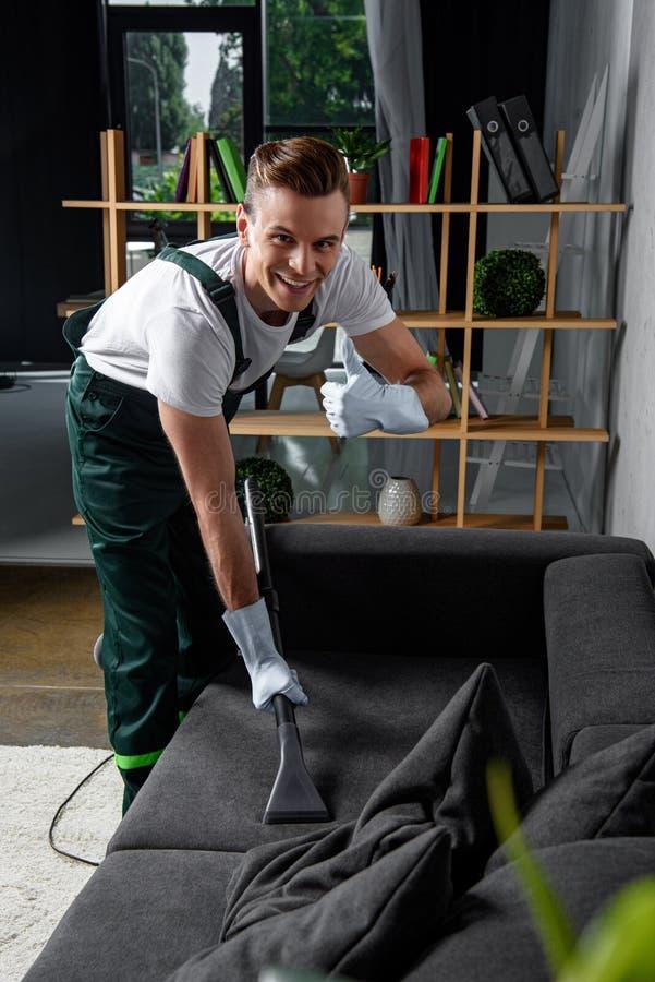 χαμόγελο του νέου καθαρίζοντας καθαρίζοντας καναπέ εργαζομένων επιχείρησης με την ηλεκτρική σκούπα και παρουσίαση στοκ εικόνες