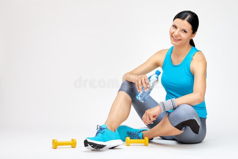 Χαμόγελο του πόσιμου νερού γυναικών στη γυμναστική στοκ εικόνα