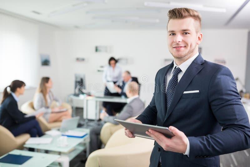 Χαμόγελο του υπολογιστή ταμπλετών εκμετάλλευσης επιχειρηματιών στην αίθουσα συνεδριάσεων στοκ φωτογραφίες