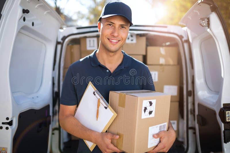 Χαμόγελο των κιβωτίων φόρτωσης ατόμων παράδοσης στο φορτηγό του στοκ εικόνες με δικαίωμα ελεύθερης χρήσης