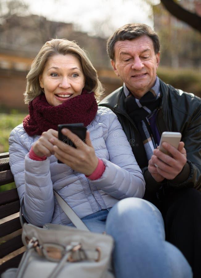 Χαμόγελο ώριμο με τα κινητά τηλέφωνα στοκ φωτογραφία με δικαίωμα ελεύθερης χρήσης