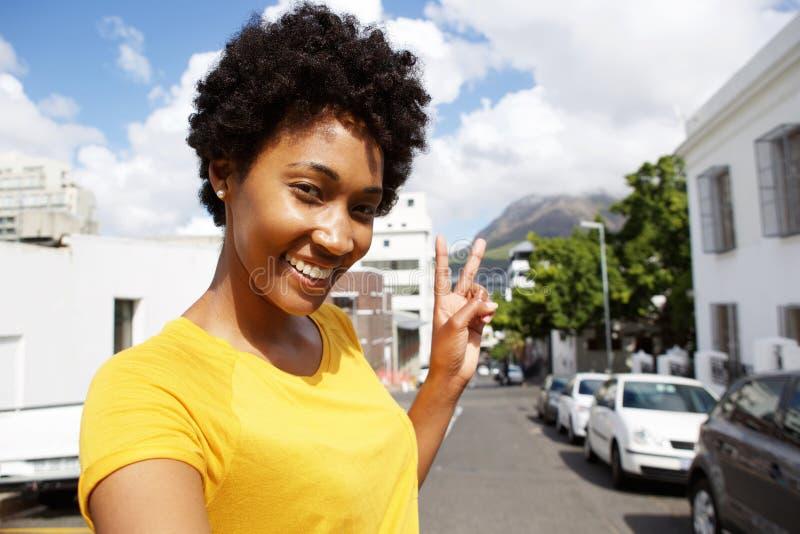 Χαμόγελου νέο σημάδι ειρήνης γυναικών gesturing στοκ εικόνες