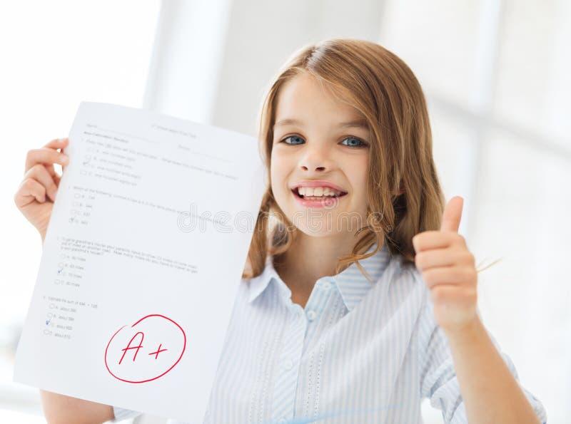 Χαμόγελο λίγου κοριτσιού σπουδαστών με τη δοκιμή και το βαθμό Α στοκ εικόνες