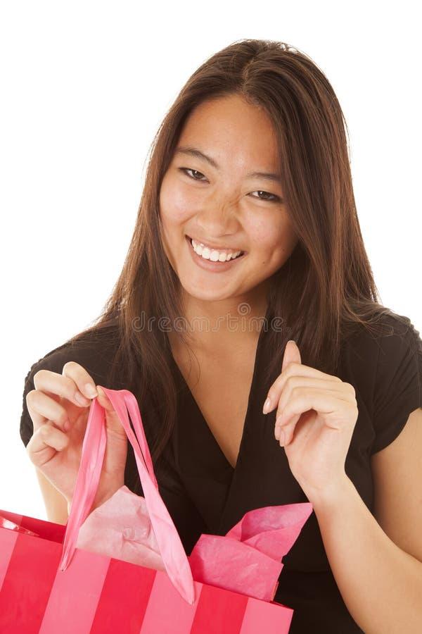 Χαμόγελο γυναικών που φαίνεται ρόδινη τσάντα στοκ εικόνες