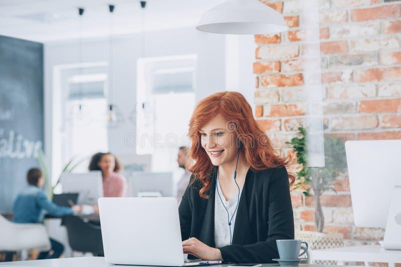 Χαμόγελο επιχειρηματιών που λειτουργεί στο lap-top στοκ φωτογραφία