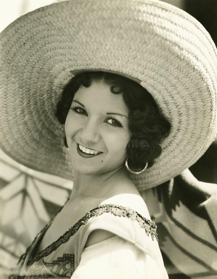Χαμόγελο κάτω από το καπέλο αχύρου της στοκ εικόνες