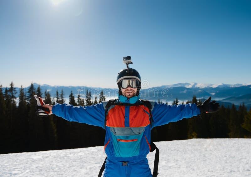 χαμόγελο σκιέρ μια ηλιόλουστη ημέρα Ενάντια στο σκηνικό των βουνών στοκ εικόνες με δικαίωμα ελεύθερης χρήσης