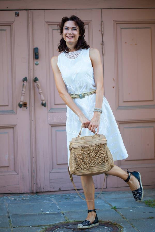 Χαμόγελο της αρκετά μέσης ηλικίας γυναίκας στο άσπρο φόρεμα στοκ εικόνες