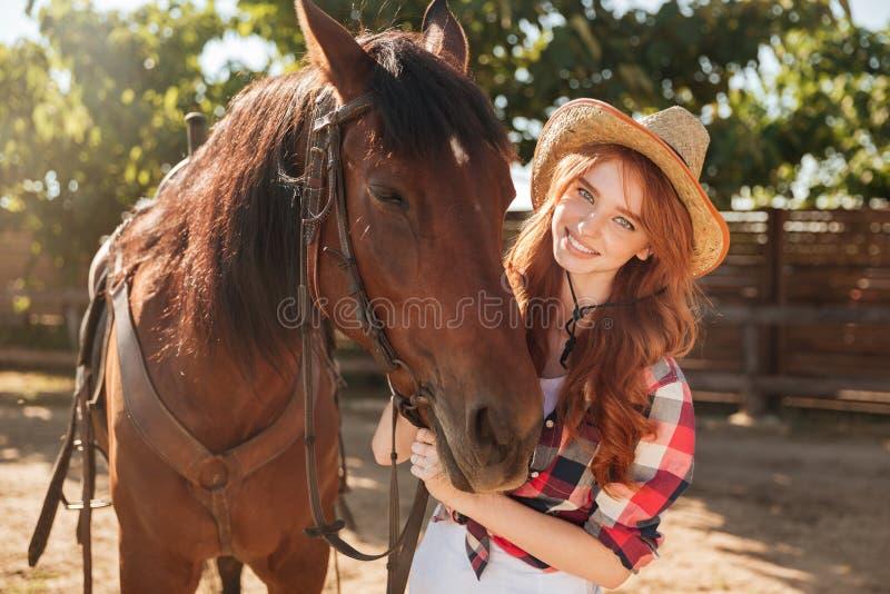 Χαμόγελο της αρκετά νέας γυναίκας cowgirl στο καπέλο με το άλογό της στοκ εικόνα με δικαίωμα ελεύθερης χρήσης