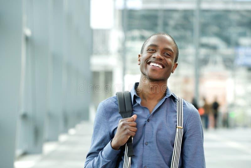 Χαμόγελο της αφρικανικής μόνιμης τσάντας επιχειρηματιών στην οικοδόμηση στοκ εικόνα