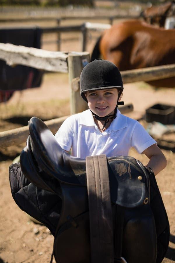 Χαμόγελο της σέλας αλόγων εκμετάλλευσης κοριτσιών στο αγρόκτημα στοκ εικόνες