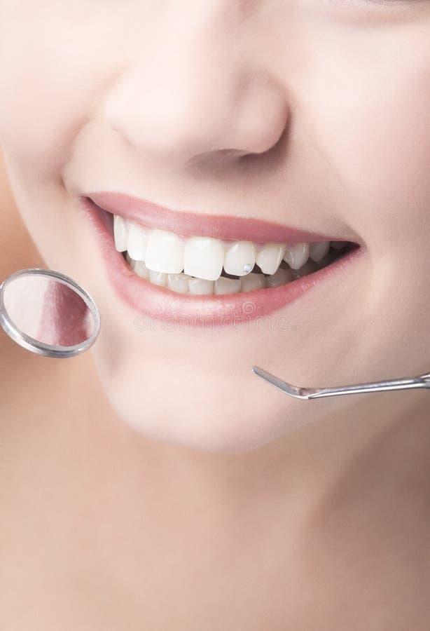 Χαμόγελο της υγιούς στοματικής κινηματογράφησης σε πρώτο πλάνο γυναικών με τον καθρέφτη και την γκέτα οδοντιάτρων στοκ εικόνες