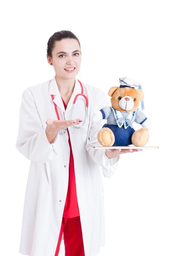 Χαμόγελο του θηλυκού γιατρού που παρουσιάζει το παιχνίδι βελούδου στοκ φωτογραφία με δικαίωμα ελεύθερης χρήσης