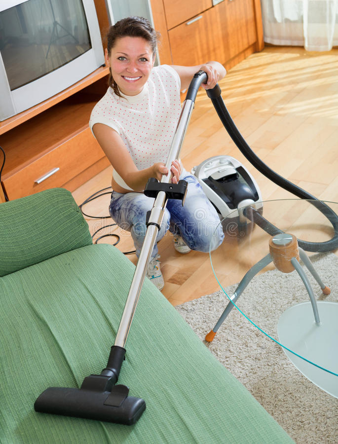 Χαμόγελο του θηλυκού καθαρίζοντας καναπέ με το hoover στοκ εικόνα με δικαίωμα ελεύθερης χρήσης
