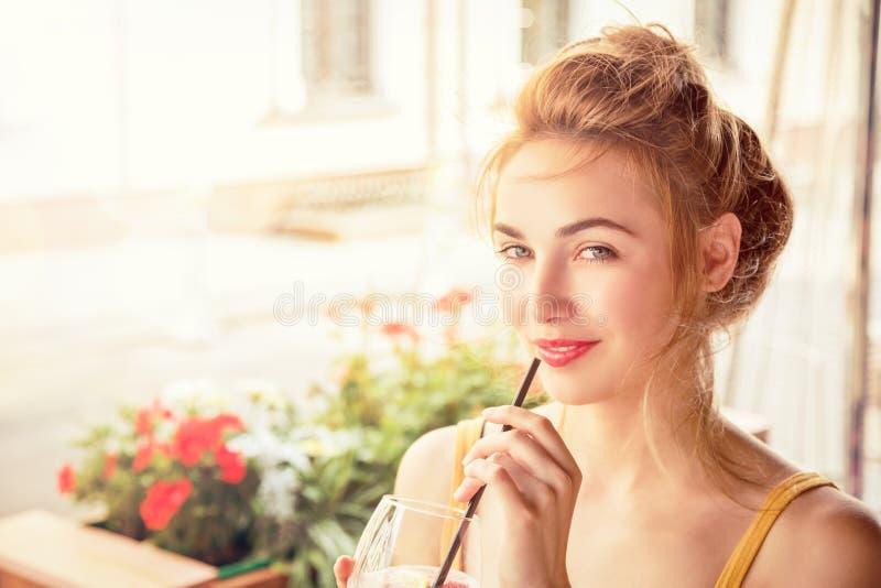 Χαμόγελο του κοκτέιλ κατανάλωσης κοριτσιών μόδας σε έναν καφέ στοκ φωτογραφία με δικαίωμα ελεύθερης χρήσης
