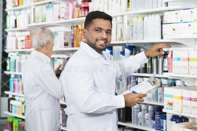 Χαμόγελο του μετρώντας αποθέματος φαρμακοποιών με το συνάδελφο στο φαρμακείο στοκ εικόνες με δικαίωμα ελεύθερης χρήσης