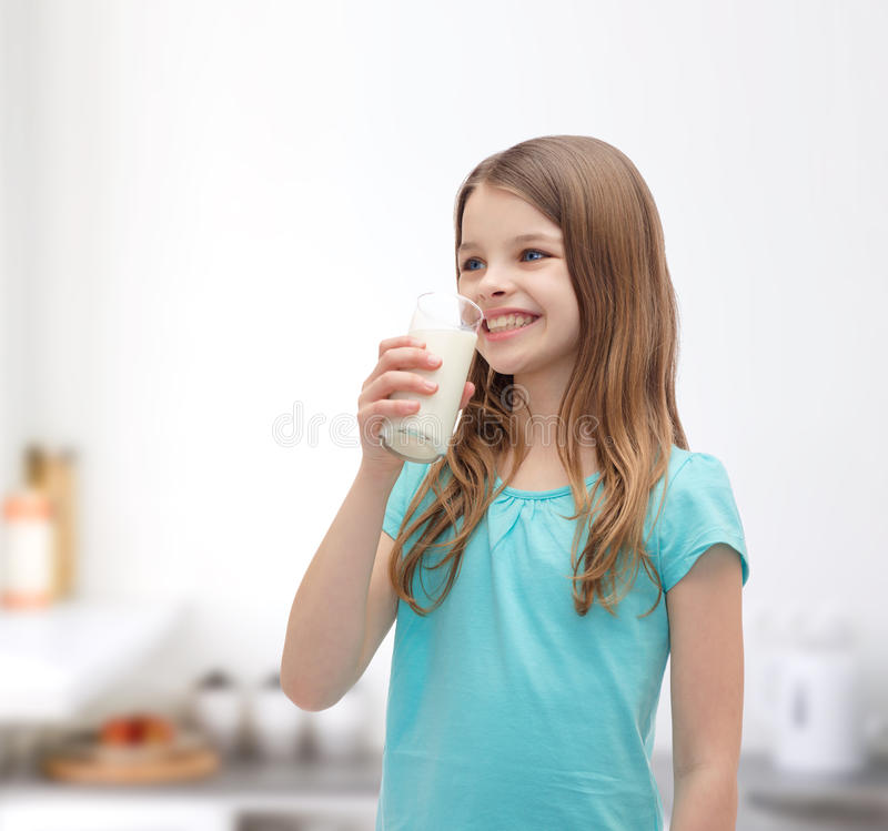 Χαμόγελο του πόσιμου γάλακτος μικρών κοριτσιών από το γυαλί στοκ εικόνα