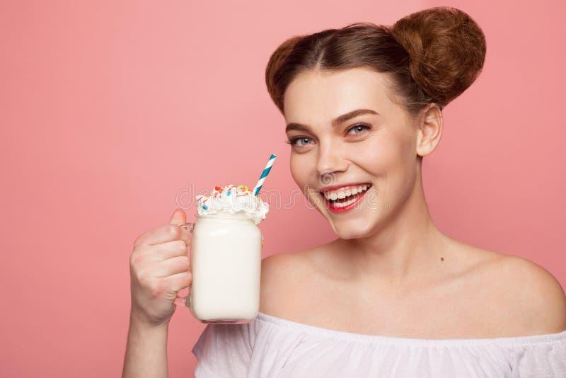 Χαμόγελο του φλυτζανιού εκμετάλλευσης κοριτσιών με το milkshake στοκ φωτογραφίες