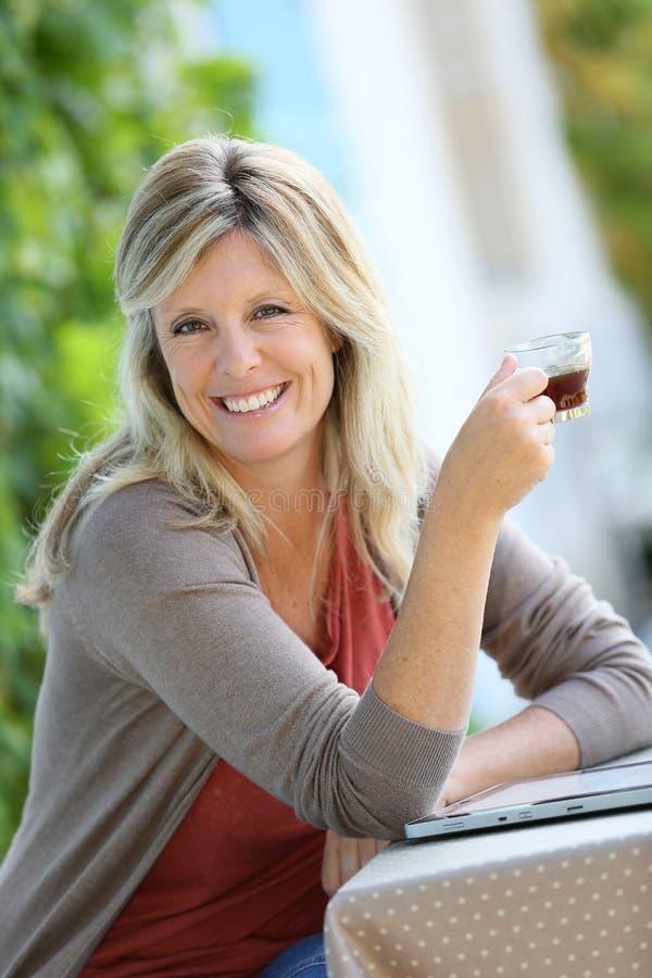Χαμόγελο του ώριμου καφέ κατανάλωσης γυναικών στον κήπο στοκ φωτογραφία με δικαίωμα ελεύθερης χρήσης