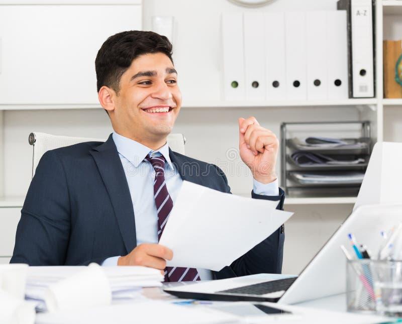 Χαμόγελο των αρσενικών εγγράφων ανάγνωσης για τη συναλλαγή στοκ φωτογραφίες με δικαίωμα ελεύθερης χρήσης