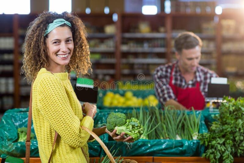 Χαμόγελο των λαχανικών αγοράς γυναικών στο οργανικό τμήμα στοκ φωτογραφία