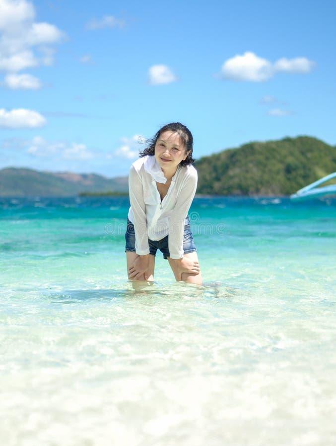 Χαμόγελο των στάσεων νέων κοριτσιών στα ρηχά νερά στοκ φωτογραφίες