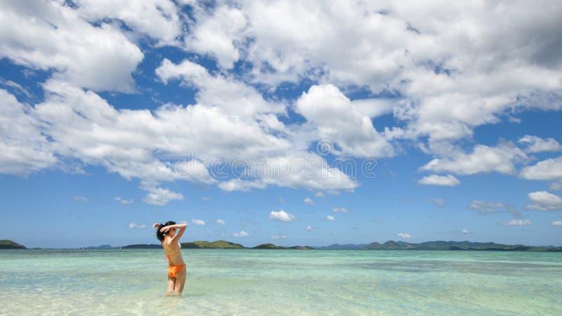 Χαμόγελο των στάσεων νέων κοριτσιών στα ρηχά νερά στοκ εικόνα με δικαίωμα ελεύθερης χρήσης