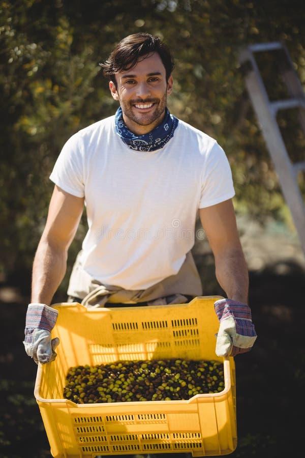 Χαμόγελο των φέρνοντας ελιών νεαρών άνδρων στο κλουβί στο αγρόκτημα στοκ φωτογραφίες με δικαίωμα ελεύθερης χρήσης