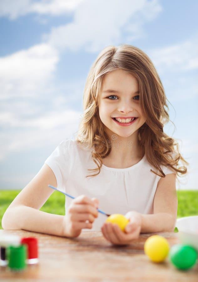 Χαμόγελο των χρωματίζοντας αυγών μικρών κοριτσιών για Πάσχα στοκ εικόνες