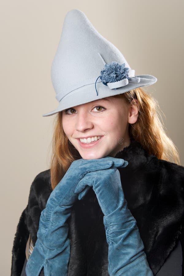 Χαμόγελο redhead με τα μπλε φορημένα γάντια σουέτ χέρια στοκ εικόνες