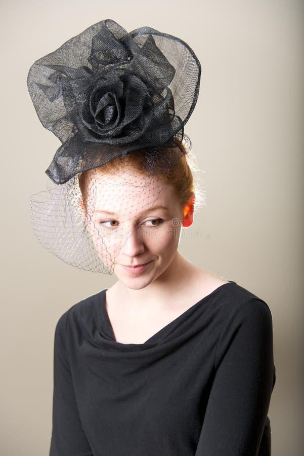 Χαμόγελο redhead στο καλυμμένο μαύρο καπέλο πλέγματος στοκ φωτογραφίες με δικαίωμα ελεύθερης χρήσης