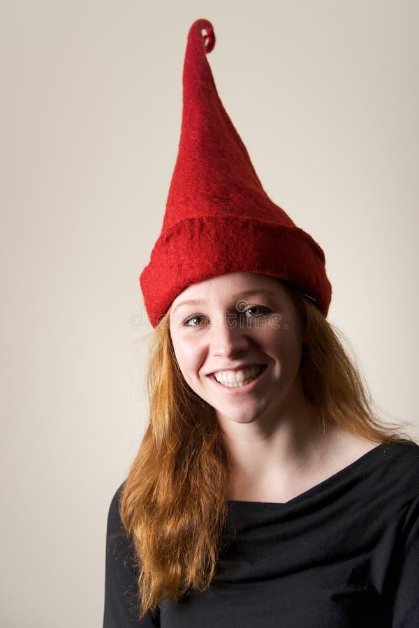 Χαμόγελο redhead στο ψηλό κόκκινο δειγμένο καπέλο στοκ φωτογραφία με δικαίωμα ελεύθερης χρήσης