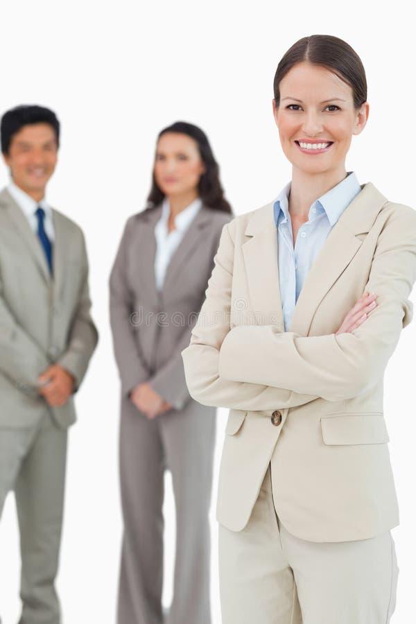 Χαμόγελο tradeswoman με τους υπαλλήλους πίσω από την στοκ εικόνες