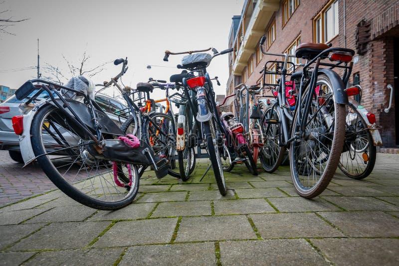 Χαοτικά σταθμευμένα εγκαταλειμμένα ποδήλατα στις οδούς των Κάτω Χωρών στοκ εικόνες με δικαίωμα ελεύθερης χρήσης